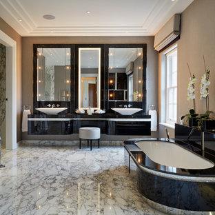 Aménagement d'une salle de bain principale contemporaine avec une vasque, un placard à porte plane, des portes de placard noires, une baignoire encastrée et un mur beige.
