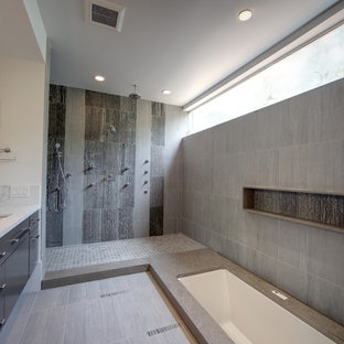 Inspiration for a large modern master gray tile and stone tile porcelain floor and gray floor bathroom remodel in Houston with an undermount sink, an undermount tub, flat-panel cabinets, black cabinets and engineered quartz countertops