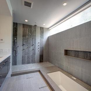Ispirazione per una grande stanza da bagno padronale moderna con lavabo sottopiano, vasca sottopiano, doccia aperta, doccia aperta, ante lisce, ante nere, piastrelle grigie, piastrelle in pietra, pavimento in gres porcellanato, top in quarzo composito e pavimento grigio