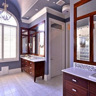 Modelo de cuarto de baño principal, clásico renovado, grande, con lavabo encastrado, armarios con paneles lisos, puertas de armario de madera en tonos medios, encimera de mármol, bañera exenta, sanitario de una pieza, baldosas y/o azulejos blancos, paredes grises y suelo de mármol
