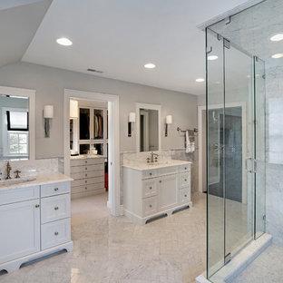 Immagine di una grande stanza da bagno padronale con ante con riquadro incassato, ante bianche, doccia ad angolo, piastrelle bianche, piastrelle di marmo, pareti marroni, pavimento in marmo, lavabo da incasso, top in marmo, pavimento bianco, porta doccia a battente e top bianco