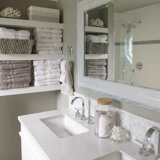 Bild på ett mellanstort maritimt en-suite badrum, med luckor med profilerade fronter, vita skåp, en dusch i en alkov, en toalettstol med separat cisternkåpa, beige kakel, keramikplattor, beige väggar, klinkergolv i porslin, ett undermonterad handfat, marmorbänkskiva, grått golv och dusch med gångjärnsdörr