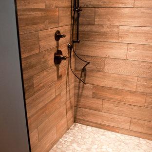 ミルウォーキーの中サイズのコンテンポラリースタイルのおしゃれなバスルーム (浴槽なし) (アンダーカウンター洗面器、落し込みパネル扉のキャビネット、中間色木目調キャビネット、御影石の洗面台、アルコーブ型シャワー、壁掛け式トイレ、ベージュのタイル、石タイル、ベージュの壁、無垢フローリング) の写真