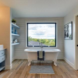 Idéer för att renovera ett mellanstort lantligt en-suite badrum, med blå skåp, ett badkar med tassar, en öppen dusch, en toalettstol med hel cisternkåpa, klinkergolv i porslin, ett avlångt handfat, marmorbänkskiva, brunt golv, med dusch som är öppen, släta luckor och blå väggar