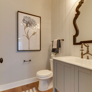 This is an example of a small country 3/4 bathroom in Minneapolis with blue cabinets, a one-piece toilet, grey walls, solid surface benchtops, medium hardwood floors, brown floor, shaker cabinets and an integrated sink.