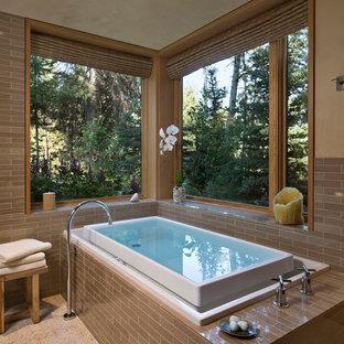 Mittelgroßes Uriges Badezimmer En Suite mit Einbaubadewanne, braunen Fliesen, Porzellanfliesen, beiger Wandfarbe, Mosaik-Bodenfliesen und beigem Boden in Sonstige