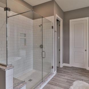 Inspiration för mellanstora klassiska en-suite badrum, med skåp i shakerstil, skåp i mörkt trä, ett fristående badkar, en dusch i en alkov, en toalettstol med separat cisternkåpa, vit kakel, porslinskakel, beige väggar, vinylgolv, ett undermonterad handfat, granitbänkskiva, grått golv och dusch med gångjärnsdörr