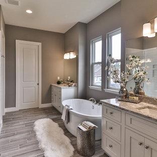 Cette photo montre une douche en alcôve principale chic de taille moyenne avec un placard à porte shaker, des portes de placard en bois sombre, une baignoire indépendante, un WC séparé, un carrelage blanc, des carreaux de porcelaine, un mur beige, un sol en vinyl, un lavabo encastré, un plan de toilette en granite, un sol gris et une cabine de douche à porte battante.