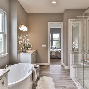 Inredning av ett klassiskt mellanstort en-suite badrum, med skåp i shakerstil, skåp i mörkt trä, ett fristående badkar, en dusch i en alkov, en toalettstol med separat cisternkåpa, vit kakel, porslinskakel, beige väggar, vinylgolv, ett undermonterad handfat, granitbänkskiva, grått golv och dusch med gångjärnsdörr