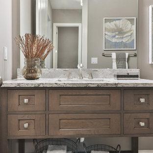 セントルイスの中サイズのトランジショナルスタイルのおしゃれなバスルーム (浴槽なし) (シェーカースタイル扉のキャビネット、濃色木目調キャビネット、アルコーブ型浴槽、シャワー付き浴槽、分離型トイレ、白いタイル、磁器タイル、ベージュの壁、クッションフロア、アンダーカウンター洗面器、御影石の洗面台、グレーの床、シャワーカーテン) の写真