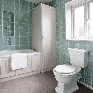 Modelo de cuarto de baño infantil, tradicional, de tamaño medio, con armarios con paneles empotrados, puertas de armario grises, bañera encastrada, ducha esquinera, sanitario de pared, baldosas y/o azulejos verdes, baldosas y/o azulejos de porcelana, paredes verdes, suelo vinílico, lavabo encastrado y encimera de mármol