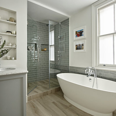 Beach style 3/4 gray tile beige floor bathroom photo in London with gray cabinets, white walls, an undermount sink, a hinged shower door and gray countertops