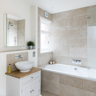 Medium sized victorian family bathroom in London with freestanding cabinets, white cabinets, a built-in bath, a shower/bath combination, a two-piece toilet, beige tiles, travertine tiles, beige walls, travertine flooring, a vessel sink, wooden worktops, beige floors and a hinged door.