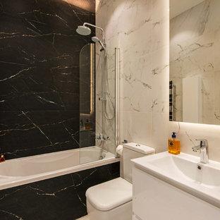 Ejemplo de cuarto de baño infantil, actual, de tamaño medio, con puertas de armario blancas, jacuzzi, sanitario de una pieza, baldosas y/o azulejos blancas y negros, baldosas y/o azulejos de porcelana y suelo de baldosas de porcelana