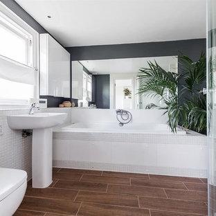 ロンドンの大きいモダンスタイルのおしゃれな子供用バスルーム (フラットパネル扉のキャビネット、白いキャビネット、ドロップイン型浴槽、オープン型シャワー、壁掛け式トイレ、白いタイル、セラミックタイル、グレーの壁、竹フローリング、ペデスタルシンク、タイルの洗面台、茶色い床、引戸のシャワー、白い洗面カウンター) の写真