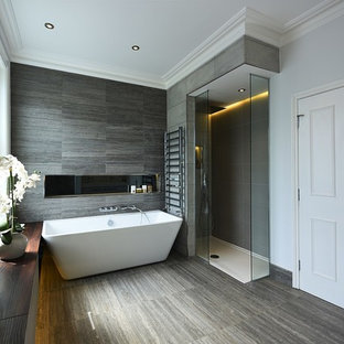 This is an example of a medium sized contemporary family bathroom in London with flat-panel cabinets, brown cabinets, a freestanding bath, a walk-in shower, a wall mounted toilet, grey tiles, ceramic tiles, white walls, ceramic flooring, a built-in sink, quartz worktops, grey floors, an open shower and white worktops.