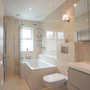 Diseño de cuarto de baño infantil, contemporáneo, pequeño, con puertas de armario beige, bañera esquinera, combinación de ducha y bañera, sanitario de pared, baldosas y/o azulejos beige, baldosas y/o azulejos de porcelana, paredes beige, suelo de mármol, lavabo suspendido, encimera de azulejos, suelo beige, ducha con puerta con bisagras y encimeras beige