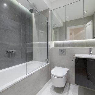 オックスフォードシャーの中サイズのコンテンポラリースタイルのおしゃれなバスルーム (浴槽なし) (ガラス扉のキャビネット、茶色いキャビネット、オープン型シャワー、壁掛け式トイレ、グレーのタイル、大理石タイル、グレーの壁、磁器タイルの床、壁付け型シンク、珪岩の洗面台、グレーの床、オープンシャワー) の写真