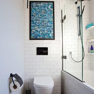 Exempel på ett litet modernt badrum för barn, med släta luckor, vita skåp, ett platsbyggt badkar, en dusch/badkar-kombination, en toalettstol med hel cisternkåpa, vit kakel, porslinskakel, vita väggar, cementgolv, ett väggmonterat handfat, bänkskiva i akrylsten, flerfärgat golv och dusch med gångjärnsdörr