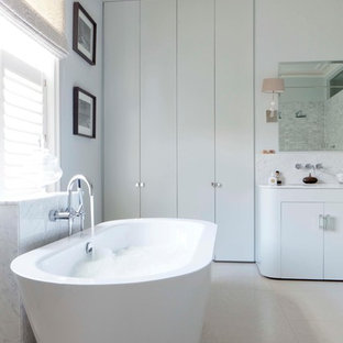 Inspiration for a contemporary bathroom in London with flat-panel cabinets, white cabinets, a freestanding bath and grey walls.