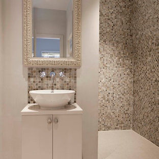 Example of a trendy beige tile and mosaic tile walk-in shower design in London with a vessel sink, flat-panel cabinets, white cabinets and beige walls