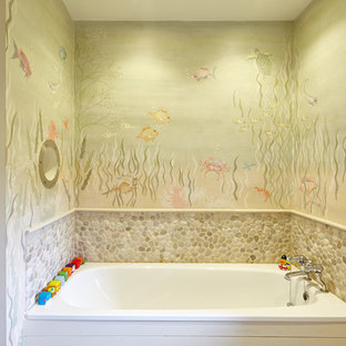 Inredning av ett exotiskt badrum för barn, med ett platsbyggt badkar och flerfärgade väggar