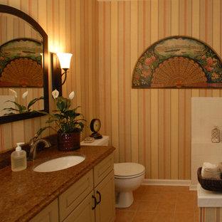 オレンジカウンティの中サイズのカントリー風おしゃれなバスルーム (浴槽なし) (レイズドパネル扉のキャビネット、ベージュのキャビネット、黄色い壁、アンダーカウンター洗面器、オレンジの床) の写真