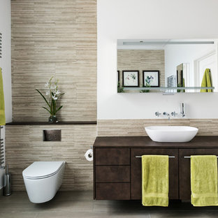 Inspiration for a contemporary ensuite bathroom in London with flat-panel cabinets, brown cabinets, a wall mounted toilet, beige tiles, white walls, a vessel sink and grey floors.