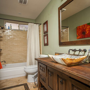 This is an example of a mid-sized transitional bathroom in Los Angeles with furniture-like cabinets, dark wood cabinets, an alcove tub, a shower/bathtub combo, a one-piece toilet, multi-coloured tile, stone tile, grey walls, travertine floors, a vessel sink and copper benchtops.