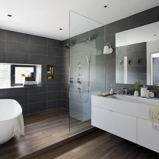 Bathroom - mid-sized contemporary master gray tile medium tone wood floor and brown floor bathroom idea in Boston with a trough sink, flat-panel cabinets, white cabinets, quartz countertops and gray walls