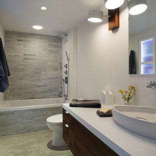 Foto di una stanza da bagno padronale design di medie dimensioni con lavabo a bacinella, ante lisce, ante in legno bruno, top in quarzo composito, vasca ad alcova, vasca/doccia, WC monopezzo, piastrelle grigie, pareti bianche, pavimento in cemento e piastrelle in pietra