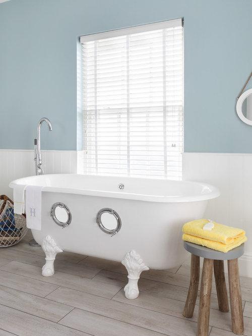 mid sized beach style master light wood floor and beige floor claw foot bathtub