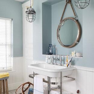 Réalisation d'une petite salle de bain principale marine avec un mur bleu, un sol en bois clair et un plan vasque.