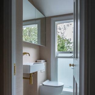 Foto de cuarto de baño infantil, moderno, de tamaño medio, con ducha abierta, sanitario de pared, baldosas y/o azulejos rosa, paredes rosas, suelo de baldosas de cerámica, lavabo suspendido, encimera de acrílico, suelo gris, ducha abierta y encimeras rosas