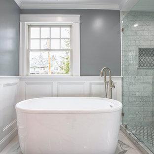 Idéer för stora vintage vitt en-suite badrum, med skåp i shakerstil, vita skåp, ett fristående badkar, en dusch i en alkov, en toalettstol med hel cisternkåpa, vit kakel, marmorkakel, grå väggar, klinkergolv i porslin, ett undermonterad handfat, marmorbänkskiva, vitt golv och dusch med skjutdörr