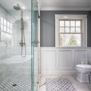 Bild på ett stort vintage vit vitt en-suite badrum, med skåp i shakerstil, vita skåp, ett fristående badkar, en dusch i en alkov, en toalettstol med hel cisternkåpa, vit kakel, marmorkakel, grå väggar, klinkergolv i porslin, ett undermonterad handfat, marmorbänkskiva, vitt golv och dusch med skjutdörr