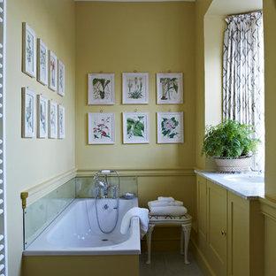 Idee per una stanza da bagno chic con lavabo sottopiano, ante in stile shaker, ante gialle, vasca da incasso e pareti gialle