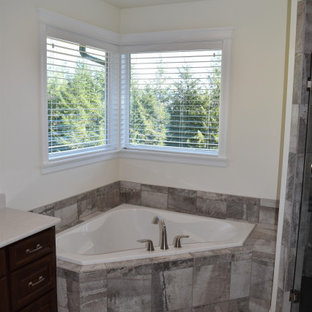 Mid-sized elegant master gray tile and porcelain tile porcelain floor, gray floor, double-sink and brick wall bathroom photo in Portland with raised-panel cabinets, dark wood cabinets, a two-piece toilet, white walls, an undermount sink, quartzite countertops, a hinged shower door, white countertops and a built-in vanity