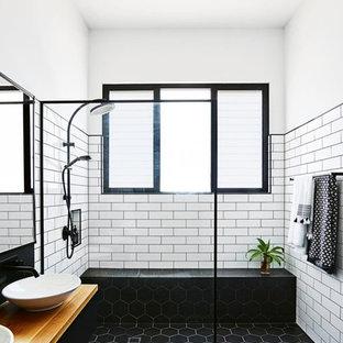 Ispirazione per una stanza da bagno con doccia industriale di medie dimensioni con ante nere, doccia a filo pavimento, piastrelle bianche, pareti bianche, pavimento con piastrelle in ceramica, lavabo a bacinella, top in legno, pavimento nero, doccia aperta, piastrelle diamantate e top marrone