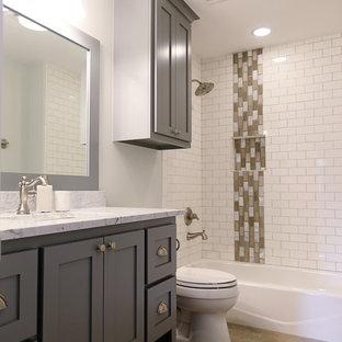 Diseño de cuarto de baño con ducha, de estilo de casa de campo, de tamaño medio, con armarios estilo shaker, puertas de armario grises, baldosas y/o azulejos blancos, baldosas y/o azulejos de cemento, paredes blancas, lavabo bajoencimera, encimera de cuarcita, bañera empotrada, combinación de ducha y bañera, suelo vinílico y sanitario de dos piezas