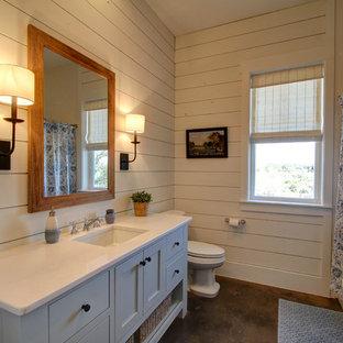 Foto på ett lantligt badrum, med skåp i shakerstil, blå skåp, ett platsbyggt badkar, en toalettstol med separat cisternkåpa, vit kakel, vita väggar, betonggolv, ett undermonterad handfat och bänkskiva i kvartsit