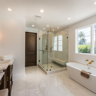 Inspiration for a mediterranean master beige tile and marble tile marble floor and beige floor bathroom remodel in Los Angeles with recessed-panel cabinets, dark wood cabinets, white walls, an undermount sink, marble countertops, a hinged shower door and beige countertops