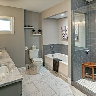 This is an example of a medium sized country ensuite bathroom in Minneapolis with flat-panel cabinets, grey cabinets, an alcove bath, an alcove shower, a two-piece toilet, grey tiles, ceramic tiles, grey walls, ceramic flooring, a submerged sink and quartz worktops.