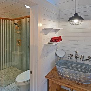 Diseño de cuarto de baño principal, de estilo de casa de campo, con armarios abiertos, puertas de armario de madera oscura, ducha a ras de suelo, sanitario de una pieza, suelo de baldosas tipo guijarro, paredes blancas, lavabo sobreencimera, encimera de madera, suelo de baldosas tipo guijarro y encimeras marrones