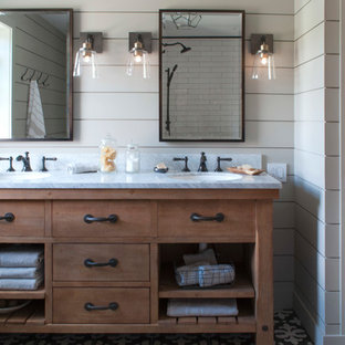 Diseño de cuarto de baño principal, de estilo de casa de campo, de tamaño medio, con armarios abiertos, puertas de armario de madera oscura, bañera empotrada, ducha empotrada, sanitario de una pieza, paredes grises, suelo de baldosas de cerámica, lavabo bajoencimera, encimera de mármol, suelo negro y ducha con cortina