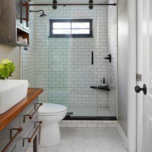 Свежая идея для дизайна: ванная комната среднего размера в стиле кантри с плоскими фасадами, синими фасадами, душем в нише, раздельным унитазом, серыми стенами, полом из керамической плитки, душевой кабиной, настольной раковиной, столешницей из дерева, белым полом, душем с раздвижными дверями, коричневой столешницей, белой плиткой и плиткой кабанчик - отличное фото интерьера