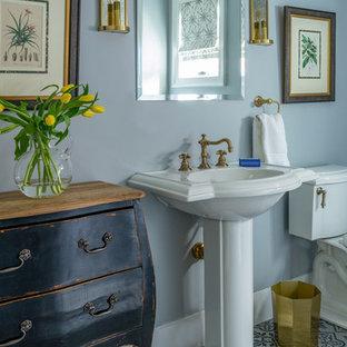 Cette image montre une très grande salle d'eau rustique avec un WC séparé, un carrelage blanc, un sol en carrelage de terre cuite, un lavabo de ferme, des portes de placard blanches, un mur bleu et un plan de toilette blanc.