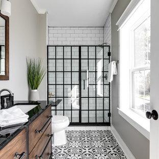 Exemple d'une douche en alcôve nature avec un placard à porte plane, des portes de placard en bois sombre, un carrelage blanc, un carrelage métro, un mur gris, un lavabo encastré, un sol multicolore, un plan de toilette noir et meuble double vasque.