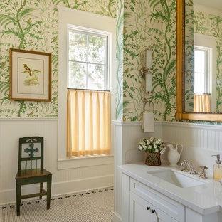 Lantlig inredning av ett badrum, med ett undermonterad handfat, möbel-liknande, vita skåp, flerfärgade väggar och mosaikgolv