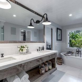Modelo de cuarto de baño principal, de estilo de casa de campo, con armarios abiertos, puertas de armario con efecto envejecido, bañera exenta, paredes grises, lavabo bajoencimera, suelo blanco y encimeras blancas